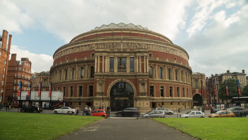 Traffic moves past London's iconic Royal Albert Hall, free of scaffolding, as clouds fly overhead.