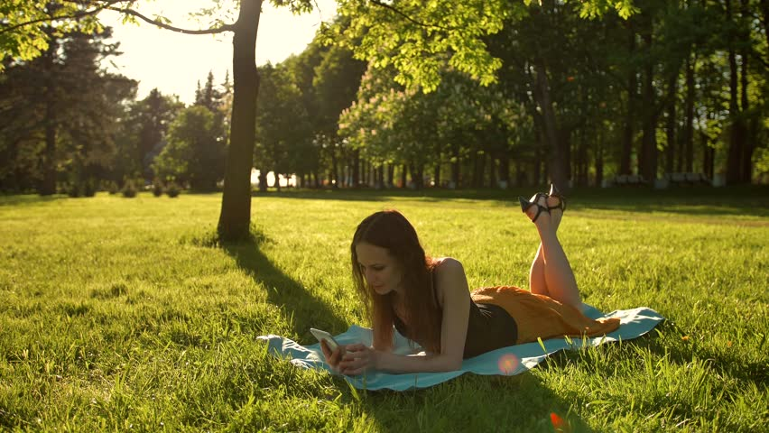 Happy young adult woman laying down over green grass while typing a message on phone. Legs swinging