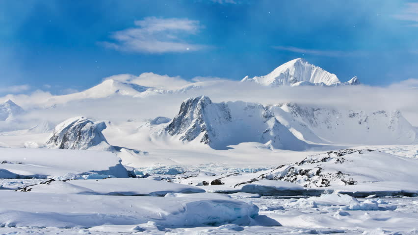 Antarctica Nature. Snow-capped mountain range against blue cloudy sky. Magestic snow winter landscape. Exploring beauty world, holidays, recreation, travel concept. 4K Slow Motion Parallax Effect