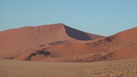 HD high quality video of red sand dunes and barchans in famous endless sand sea area of Sossusvlei Namib Desert on sunny early morning in Namib-Naulkuft Park in Namibia, southern Africa