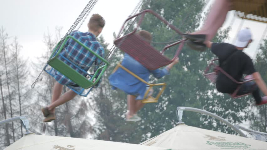 Happy teenage best friends riding the chairoplane carousel and having fun at the funfair Royalty-Free Stock Footage #1014161285
