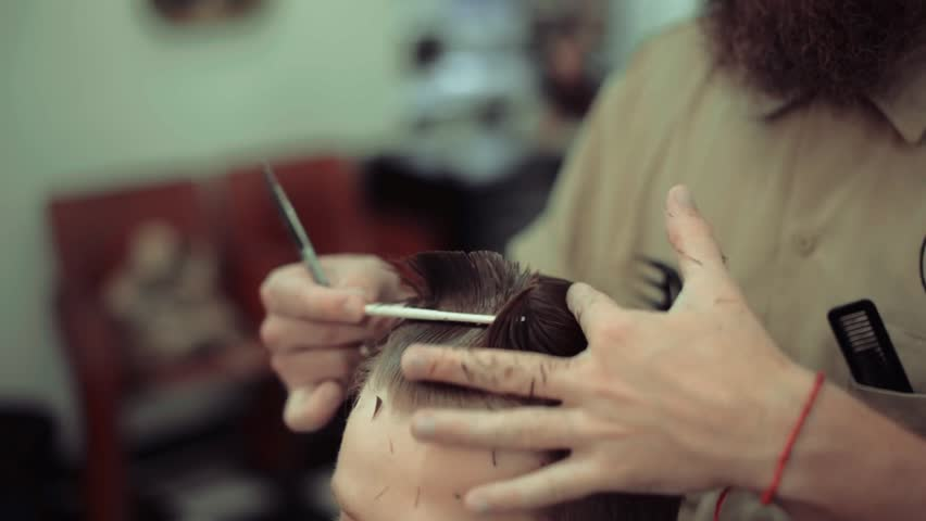 Men's haircut in barbershop. Barber makes a hairstyle and styling a client. Scissor cutting. Hair Care.   Shutterstock HD Video #1014167864