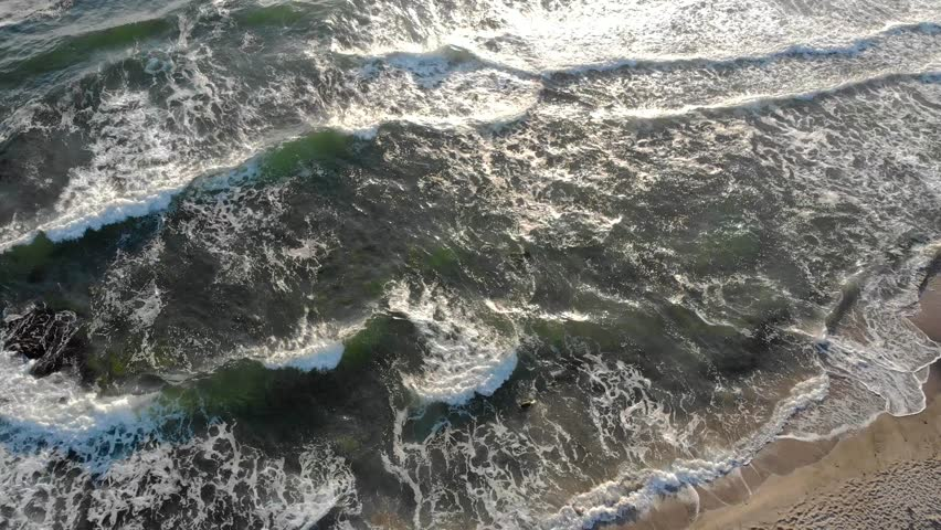 Aerial drone footage of crashing waves and sunset hitting the beach in Sinemorets Bulgaria. | Shutterstock HD Video #1014179120