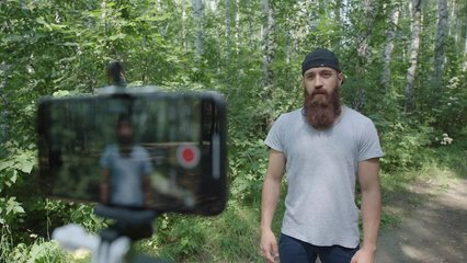 A modern sports man does the exercises and takes them off to the camera of the smartphone, recording a video blog. Sports video blog. Videoblog athlete: hipster does the exercises and shooting vlogs