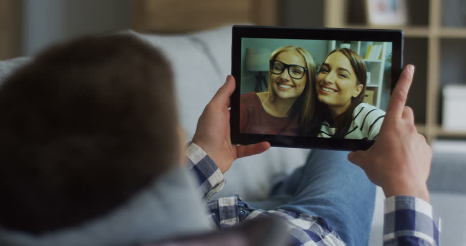 Close up of the black tablet in hands of the young man with two beautiful women on the screen while having videochat. Rear. | Shutterstock HD Video #1014201215