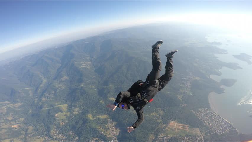 Skydiver having fun above the sea & mountains 4K