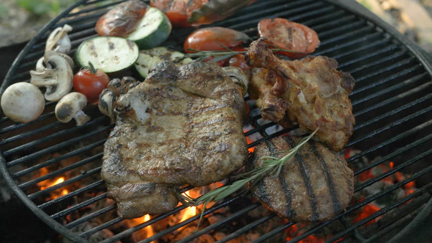Assorted meat with grilled vegetables and rosemary sprigs, in the foreground hamburger cutlet, steak on the bone, ribs, grilled vegetables, zucchini, tomatoes, mushrooms, garlic head, chef turns the   Shutterstock HD Video #1014216164