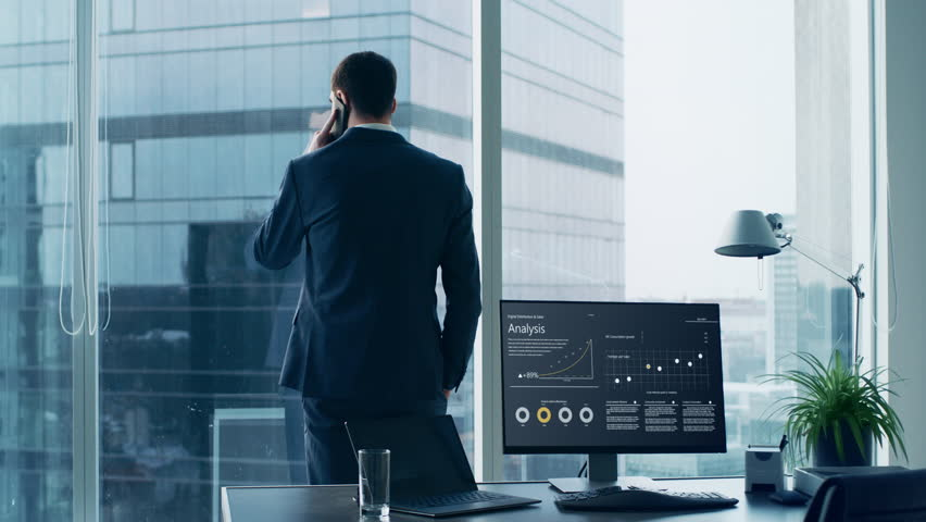 Confident Businessman in a Suit Standing in His Office, Looking out of the Window and Making Important Phone Call so He can Close the Deal.  | Shutterstock HD Video #1014231455