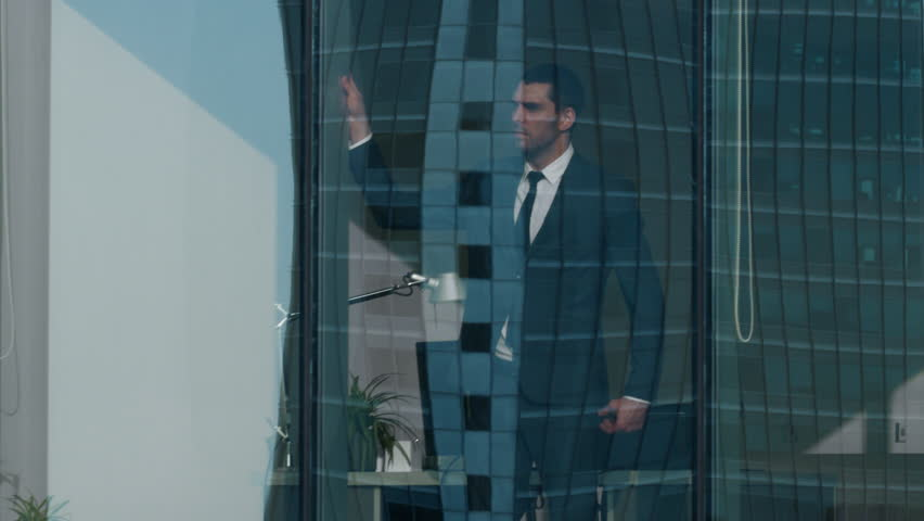 Aerial View Footage: From Outside into Office Building with Businessman Working and Looking out of the Window.
