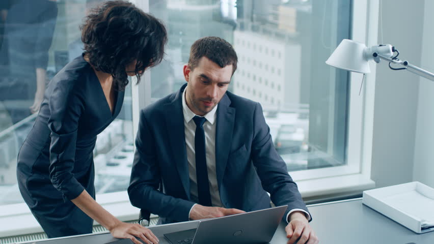In the Office Female CEO Talks with Leading Businessman who sits at His Desk, She points at Laptop Screen, They Discuss Ongoing Business Data, Contracts and Deals. In the Background Big City View. | Shutterstock HD Video #1014231584
