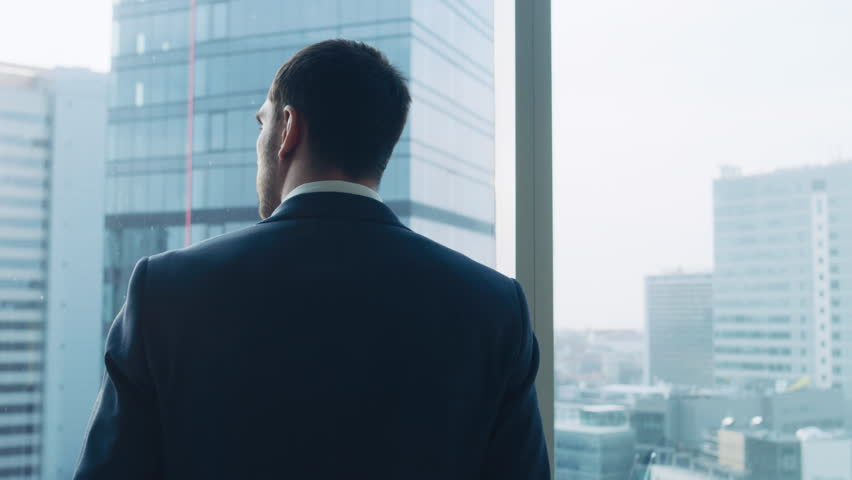 Medium Shot of Successful Businessman wearing a Suit Standing in His Office, Contemplating Next Big Business Deal, Looking out of the Window. Shot on RED EPIC-W 8K Helium Cinema Camera.