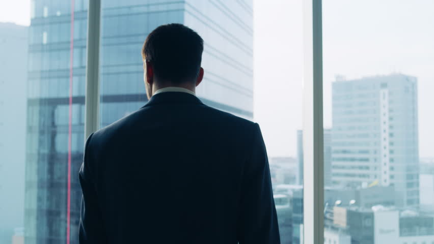 Medium Shot of Successful Businessman wearing a Suit Standing in His Office, Contemplating Next Big Business Deal, Looking out of the Window.  | Shutterstock HD Video #1014231617