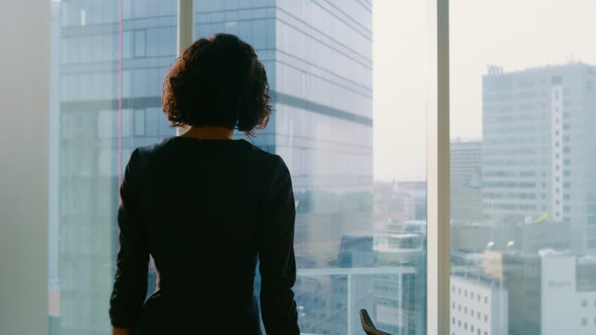 Following Shot of the Successful Businesswoman in a Stylish Dress Walking Through Her Office and Looking out of the Window Thoughtfully.  | Shutterstock HD Video #1014231644