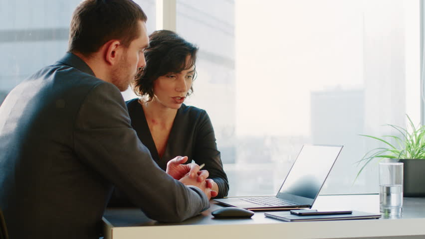 Female Top Manager and Male Businessman Sitting at the Desk Having Discussion and Working on the Laptop, Solving Problems. Shot on RED EPIC-W 8K Helium Cinema Camera.