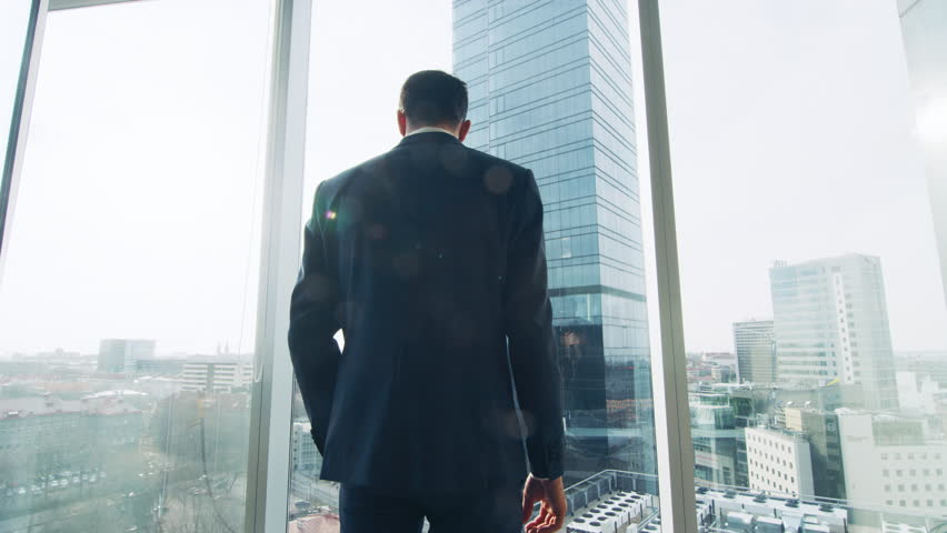Thoughtful Businessman Wearing Suit Standing in His Office, Looking out of the Window and Contemplating Next Big Business Contract. Shot on RED EPIC-W 8K Helium Cinema Camera. #1014231668