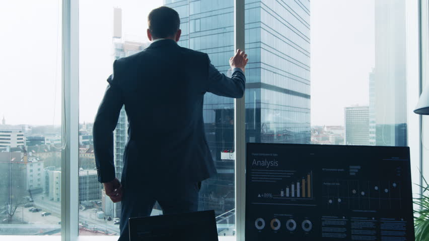 Following Shot of the Confident Businessman in a Suit Walking Through His Office and Looking out of the Window Thoughtfully. Stylish Modern Business Office with Personal Computer and Big City View. #1014231674