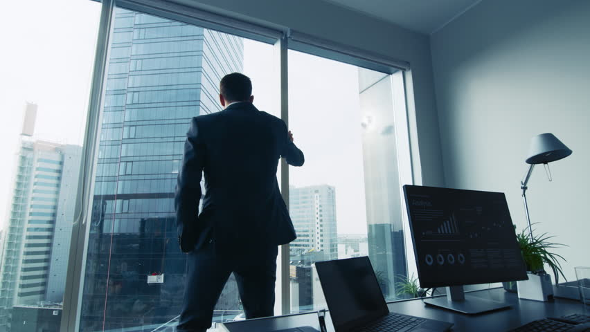 Thoughtful Businessman Wearing Suit Standing in His Office, Looking out of the Window and Contemplating Next Big Business Contract.  | Shutterstock HD Video #1014231680