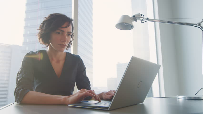 Confident Businesswoman Working on a Laptop in Her Modern Office. Stylish Beautiful Woman Doing Important Job. In the Window Big City Business District View.  | Shutterstock HD Video #1014231941