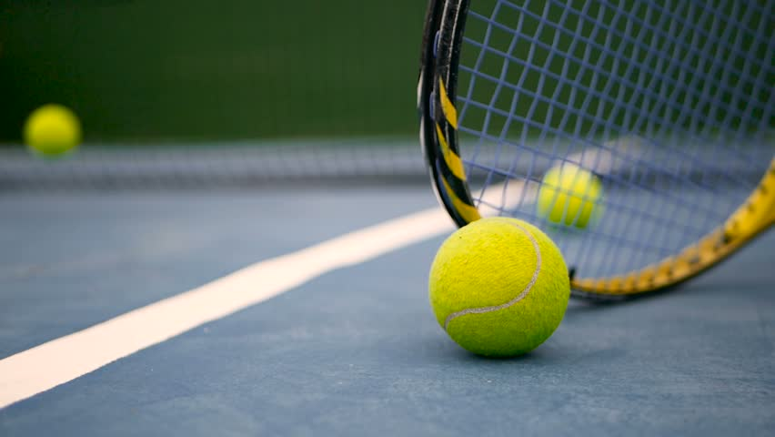 Close up of tennis equipment on the court. Sport, recreation concept. Yellow racket with a tennis ball in motion on a clay green blue court next to the white line with copy space and soft focus. #1014243899