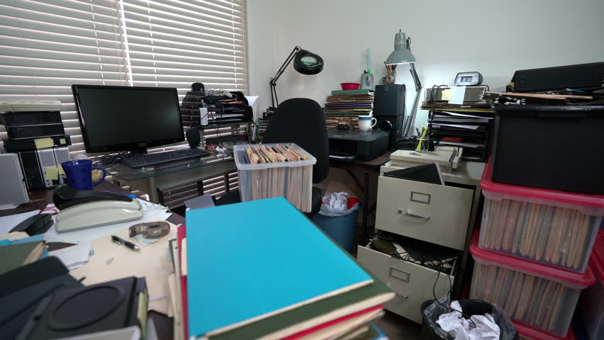 Dolly across cluttered desk in messy office with piles of files.