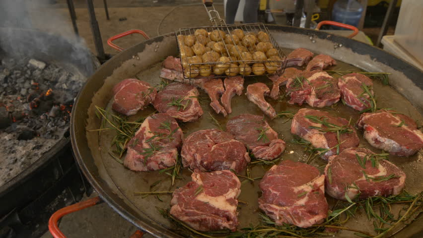 Marinated meat steaks with rosemary sprigs are laid out on a large round frying pan, potatoes for grilling, a chamber along the frying pan | Shutterstock HD Video #1014256685