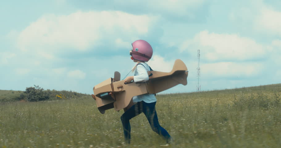 TRACKING Cute little dreamer kid girl wearing pink helmet and aviator glasses flying in a cardboard airplane through the field, pretending to be a pilot. 4K UHD 60 FPS SLO MO