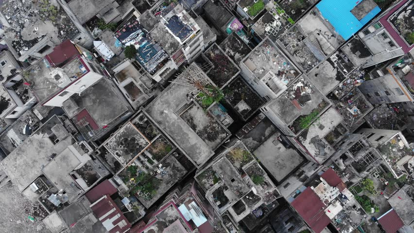 Aerial shot of old break down houses, slum area under clearance, top-down view, camera fly up. Roofs of poor housing units standing close, demolition in progress, abandoned area. #1014273956