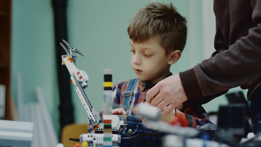 Teacher is helping and explaining little schooler how mounting wire on construction detail in robot. Classes in robotics for younger students | Shutterstock HD Video #1014274907