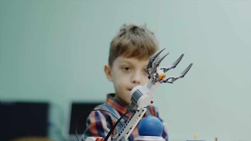 Little child boy is playing with robotic arm in a room. He is controlling it and taking ball by gadget, smiling and rejoicing