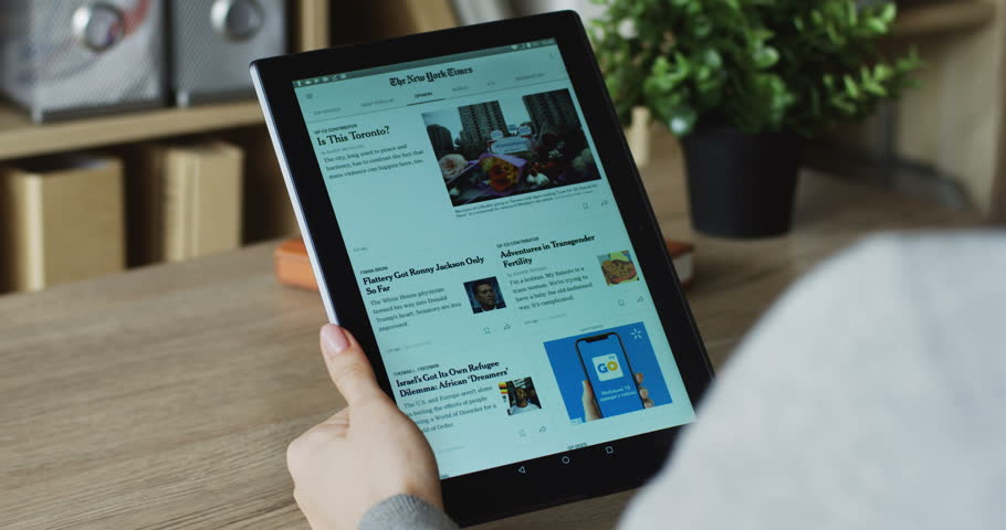 NEW YORK - January 17, 2018: view over the shoulder on the black vertical tablet device in female hands, scrolling The New York Times app and reading news.