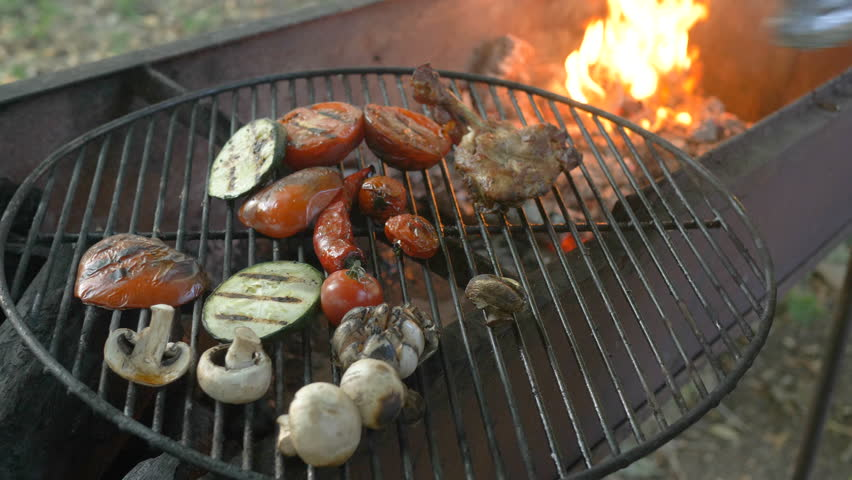 The chef takes the last piece of meat with tongs and takes the vegetables on the grill, zucchini, tomatoes, mushrooms, garlic head, the chef turns the grilled vegetables with forceps, the fire seeps   Shutterstock HD Video #1014294698