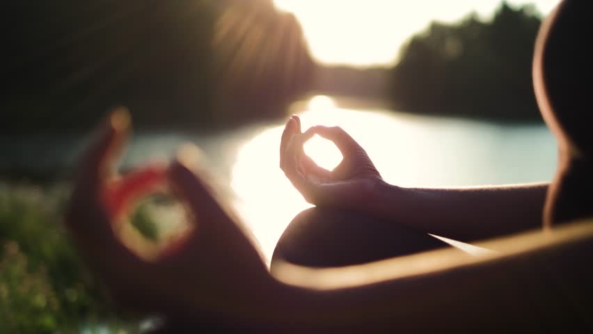 Young healthy girl practicing yoga by the lake at summer evening, shallow dof, close up on girls hand, fitness health nature energy concept, shot in 4K UHD | Shutterstock HD Video #1014306464
