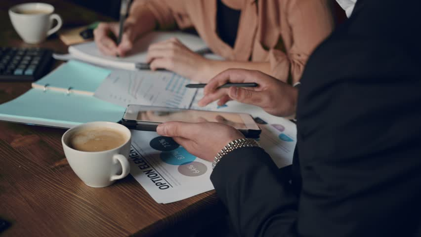 Business team office small business start up company planning creative meeting using digital tablets showing financial data and graphs. Business, people, paperwork concept Royalty-Free Stock Footage #1014318293