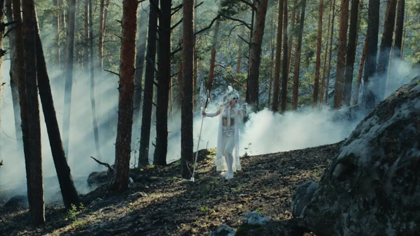 Satyr in white robe with ax axe and horns on the head appeared in the forest among trees. Wood spirit, smoke on the background. Empty wood.