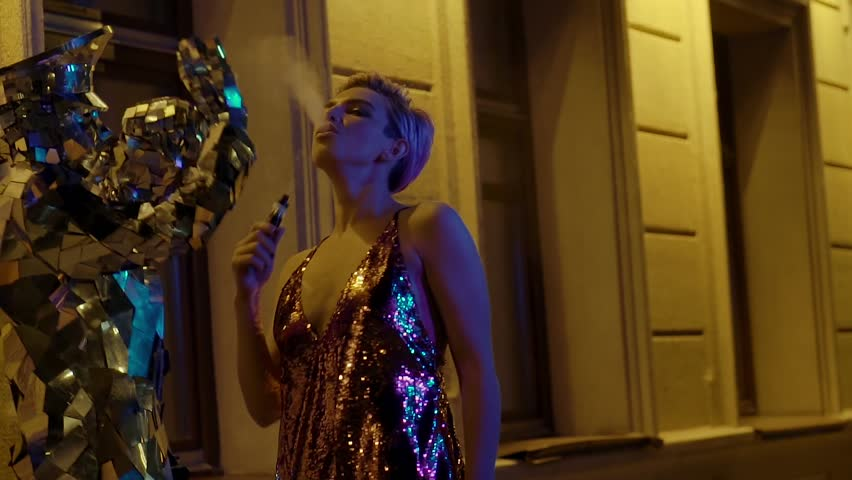 Actor in weird mirror costume dancing as young club girl passing by on the street vaping. Night life of young wild people.