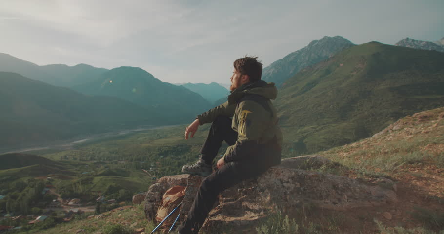 lonesome climber sitting on top of mountain. Adventurer in expedition. Freedom, zen concept 4k #1014323453