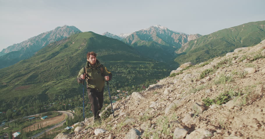 Handsome confident climber walking in mountains. Adventurer in expedition. Freedom, zen concept 4k | Shutterstock HD Video #1014323468