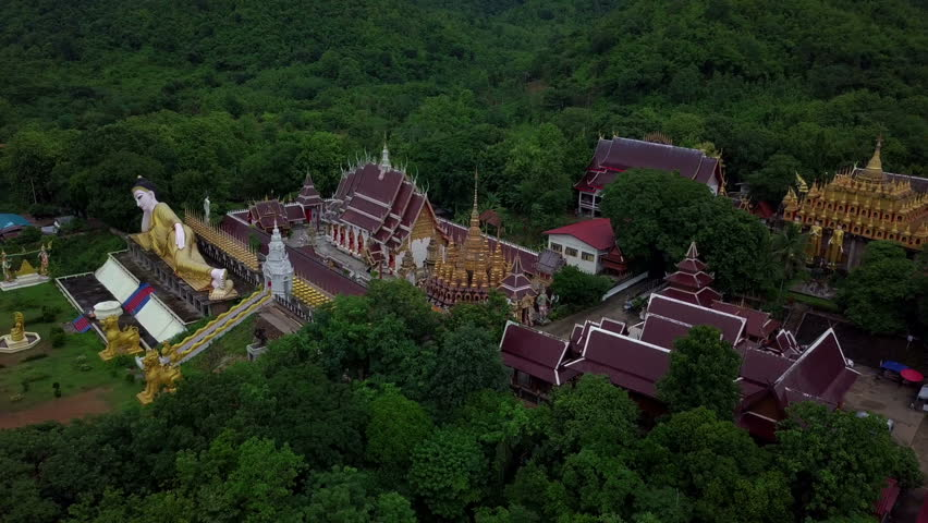 Aerial View of Buddhist Temple Wat Phra That Suthon Mongkon Khiri features beautiful architectures that are inspired by the ancient, traditional ordination hall (Ubosot) and reclining Buddha statue | Shutterstock HD Video #1014324626