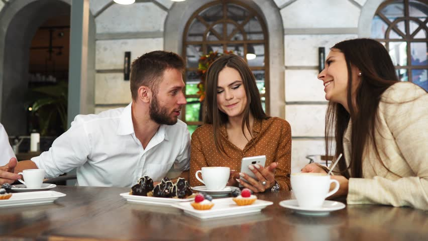 A group of men and women in office clothes sitting in a cafe at a large table and show each other in mobile phones funny pictures