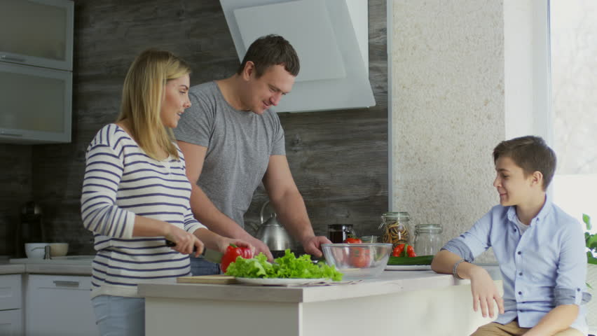 Tracking shot of mother and father cutting vegetables for salad with help of little daughter and talking with son in the kitchen | Shutterstock HD Video #1014335870