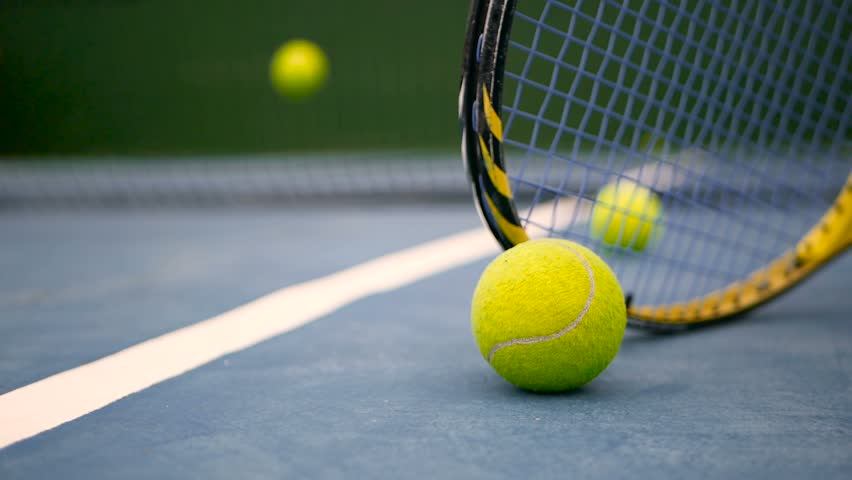Close up of tennis equipment on the court. Sport, recreation concept. Yellow racket with a tennis ball in motion on a clay green blue court next to the white line with copy space and soft focus. #1014345407