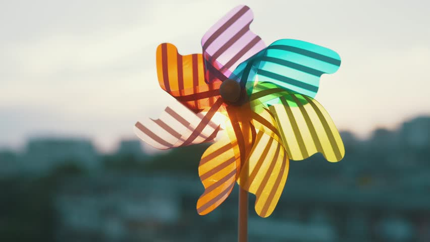 Pinwheel rotating colored plastic with blowing wind against a blue sky, white clouds, silhouettes of city buildings on sunset slow motion. Symbol of freedom and life. Toy spinner. Bright disk of sun Royalty-Free Stock Footage #1014361355