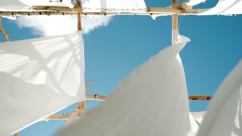 White linen cloth on wooden poles swings in the wind. Against the blue sky and green trees and fields. | Shutterstock HD Video #1014363998