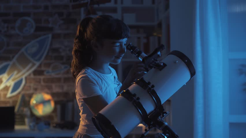 Cute girl watching the stars with a professional telescope at night in her room, imagination and childhood concept Royalty-Free Stock Footage #1014374342