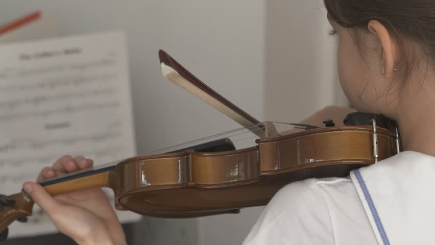Child playing violin with notes   Shutterstock HD Video #1014379973