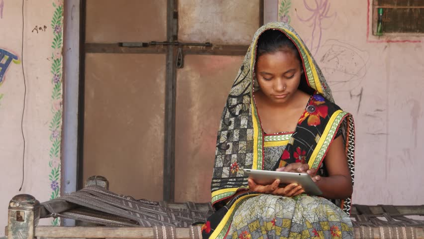 Young girl working on a touch screen tablet pad at home in a rural environment working learning studying communication network wireless confident thinking smiling positive looking at camera tilt pan