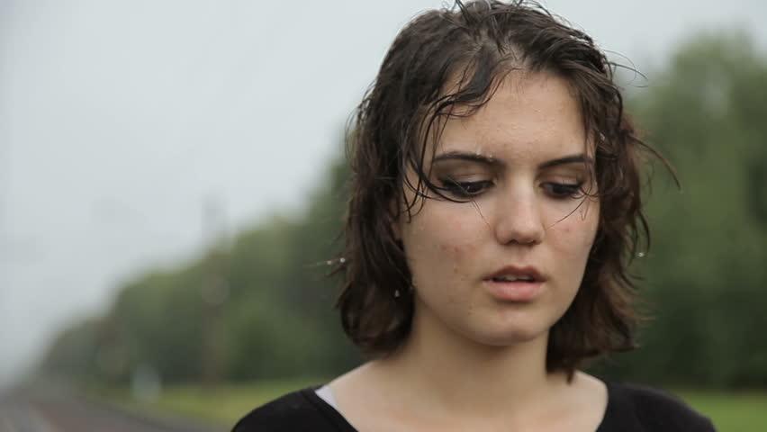 Teen girl standing in the rain