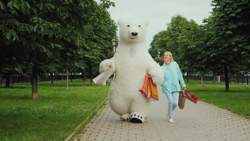 A young stylish girl is pleased with a good shopping together with her friend the big polar bear, they are cheerfully carrying the full packages of purchases