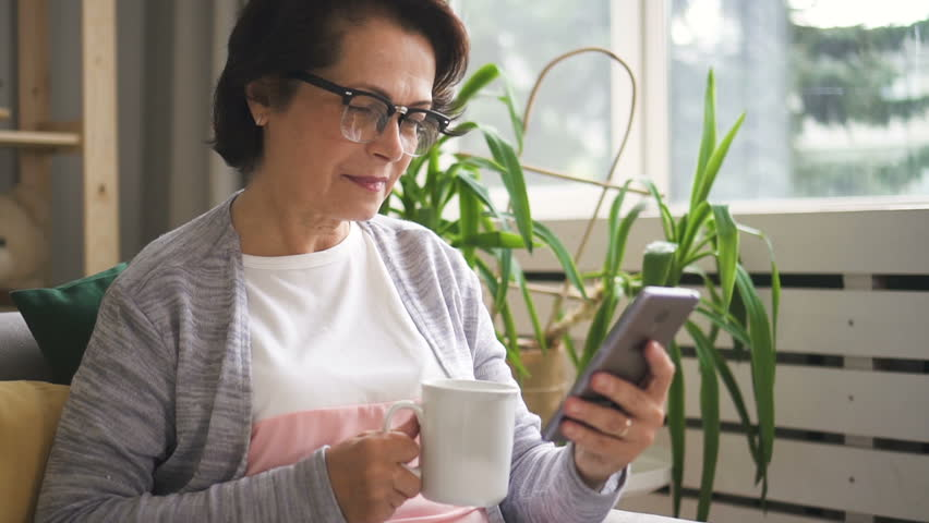 Beautiful mature woman in glasses drinking coffee from white mug, reading message on her smartphone and smiling being at home. Indoors. Portrait. | Shutterstock HD Video #1014410711