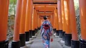 Asian women in traditional japanese kimonos walking at Fushimi Inari Shrine in Kyoto, Japan. 4K